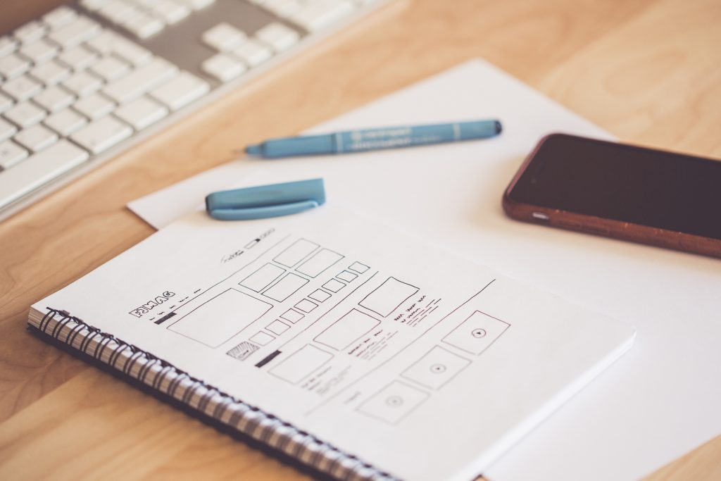 web-designer-sketching-a-wireframe-layout-ideas-in-a-notebook-adjusted